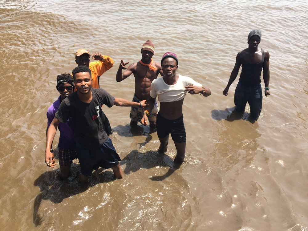 Youth at work in Kissi. Kissi is located next to one of the main water gate ways to the airport on the other side of the bay. Youth make a meager living from carrying passengers on their back to and from the boats that come in.