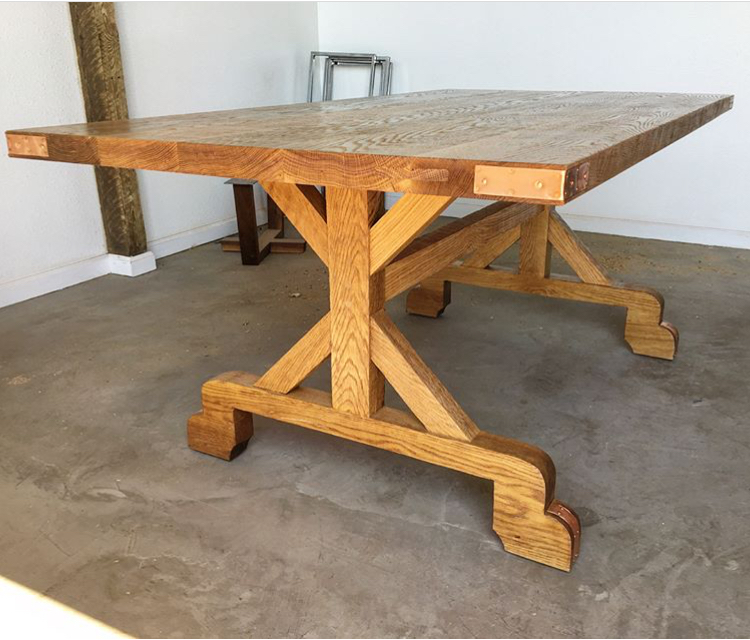 White oak farmhouse dining table with copper accents