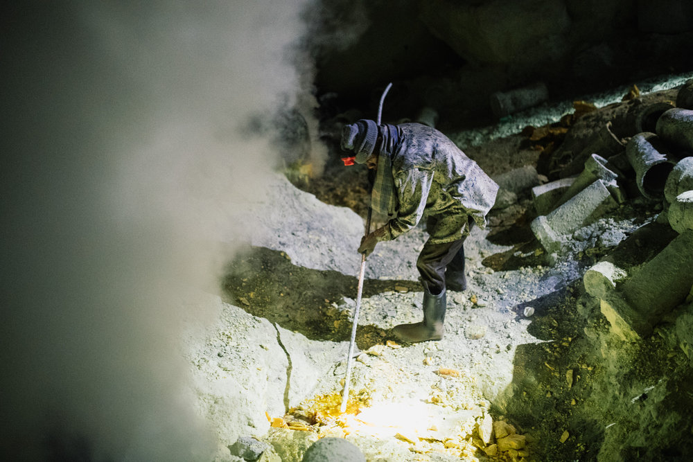 """Sulphur miner picking at the newly formed """"devil's gold"""". The gas was absolutely horrendous. This miner didn't have any facial protection.  Photo Credit: Joe Na (www.joenagraphy.com)"""