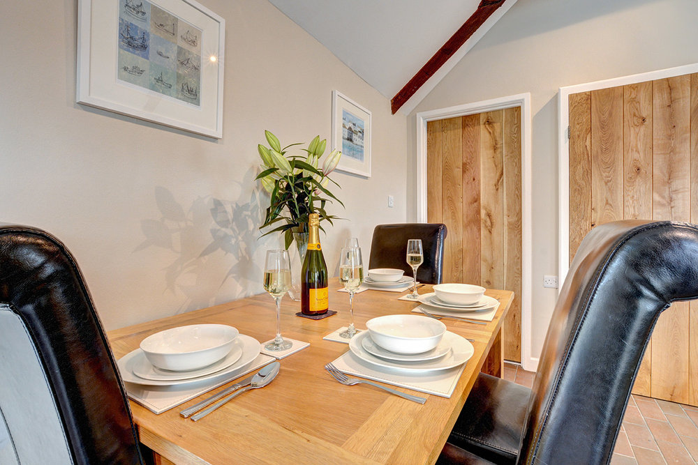 The dining area of Otterbridge luxury self catering converted barn holiday cottage at Penrose Burden in North Cornwall01.jpg