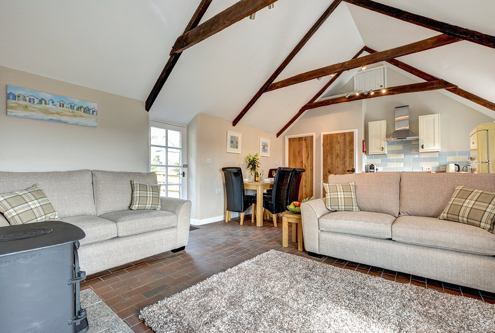 The lounge and dining area of Otterbridge luxury self catering converted barn holiday cottage at Penrose Burden in North Cornwall.jpg