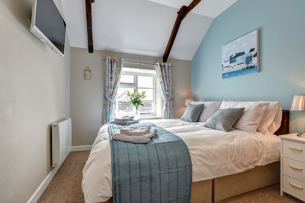 The master bedroom of Otterbridge luxury self catering converted barn holiday cottage at Penrose Burden in North Cornwall.jpg