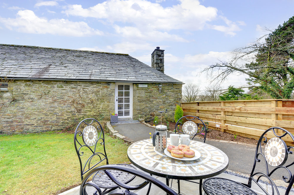 The patio and garden area outside of Otterbridge luxury self catering converted barn holiday cottage at Penrose Burden in North Cornwall.jpg