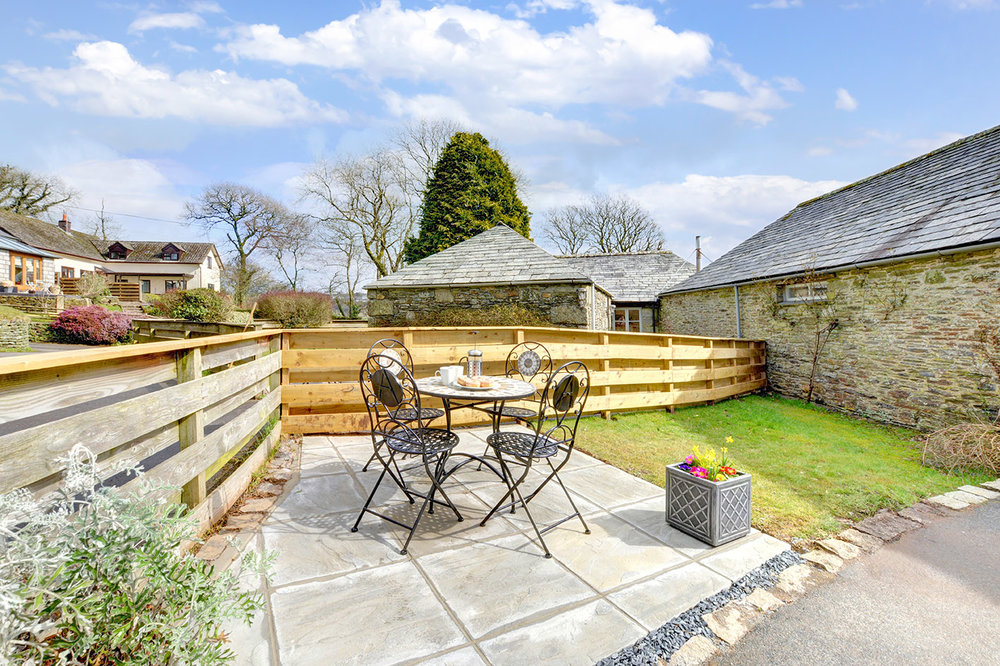 The patio and garden area outside of Otterbridge luxury self catering converted barn holiday cottage at Penrose Burden in North Cornwall01.jpg