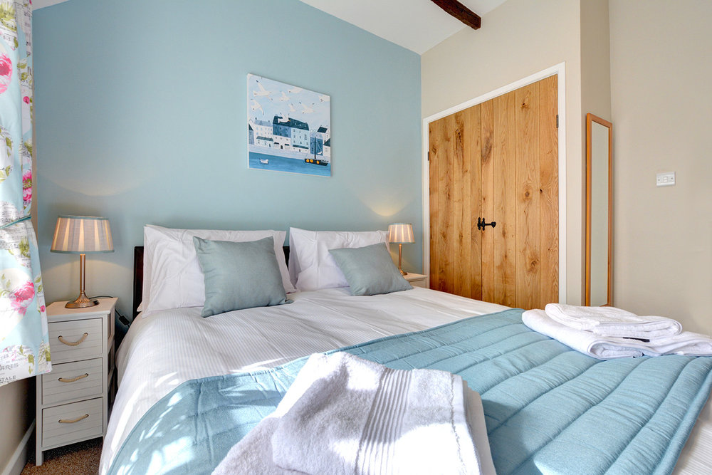 The master bedroom of Otterbridge luxury self catering converted barn holiday cottage at Penrose Burden in North Cornwall01.jpg