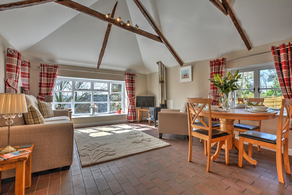 The dining and lounge area of Goosehill luxury self catering converted barn holiday cottage at Penrose Burden in North Cornwall 02.jpg