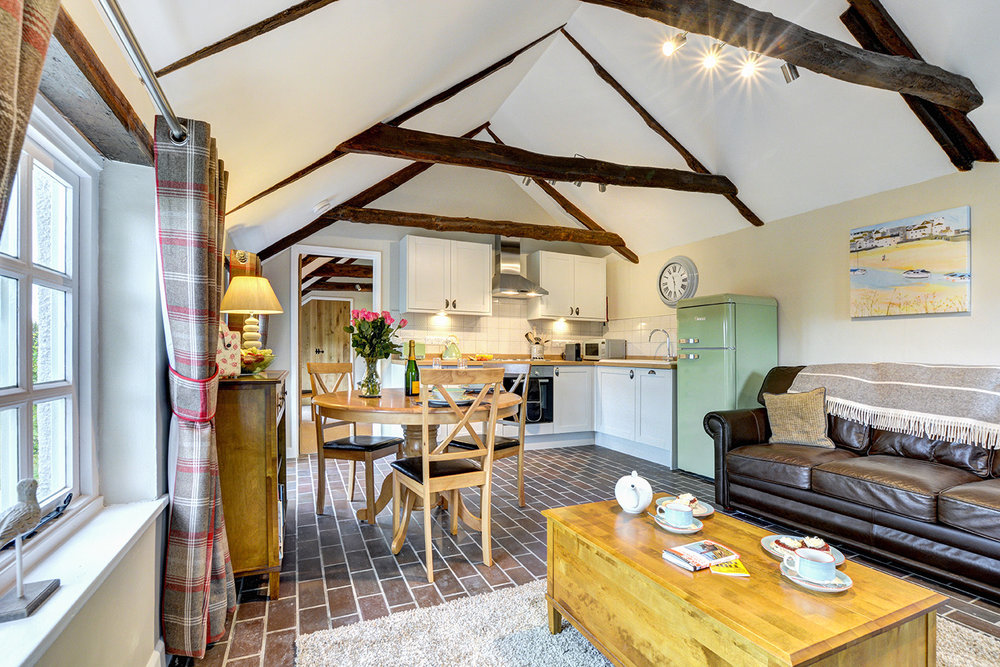 The lounge diner kitchen of The Linney self catering cottage converted barn at Penrose Burden holiday cottages in Cornwall 01.jpg