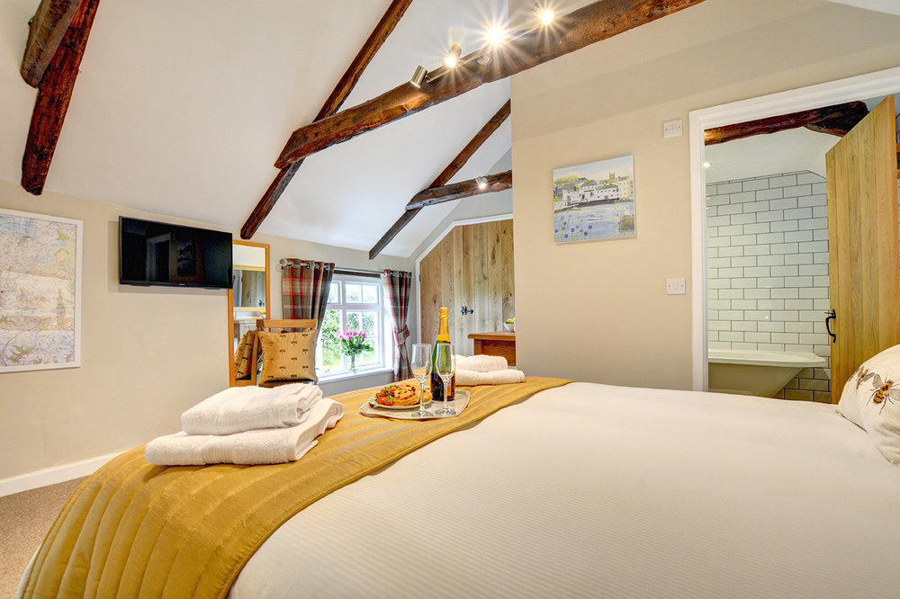 The bedroom of The Linney self catering cottage converted barn at Penrose Burden holiday cottages in Cornwall 03.jpg