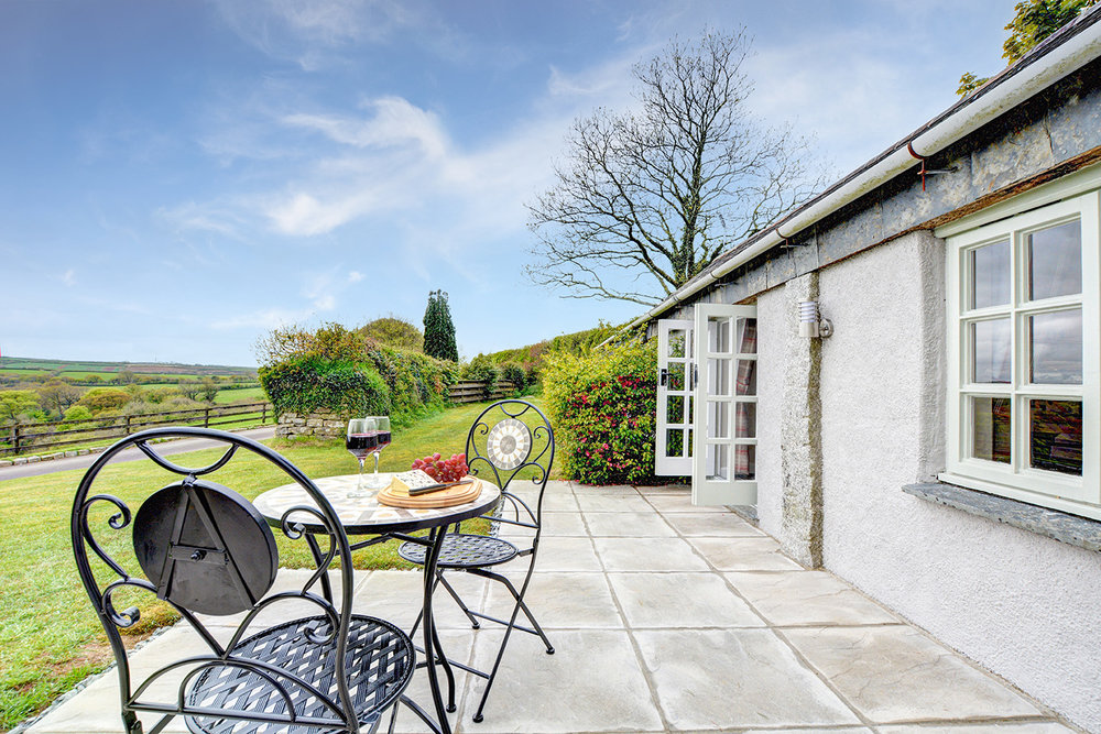The outside and patio area of The Linney self catering cottage converted barn at Penrose Burden holiday cottages in Cornwall.jpg