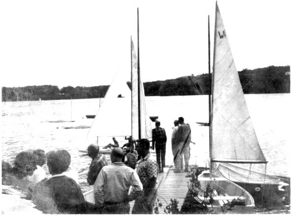 Watching racing from the dock at the right side of the boat ramp (1963). The boat   with the floorboards is a Wee Nip.