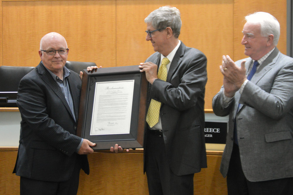Normal Engineering Director Gene Brown, left, will retire May 31. Brown received a proclamation Monday night from Normal Mayor Chris Koos, center, commemorating his career contributions to the Town. (Photo: Breanna Grow/AdaptBN)