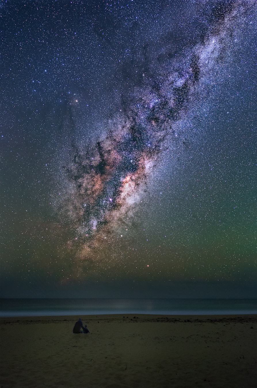 """The Milky Way rising over Dolphin Beach. 8 images stacked to reduce noise and add detail to the Milky Way. The foreground was boring so I poorly blended me and my son in for a sense of scale."""