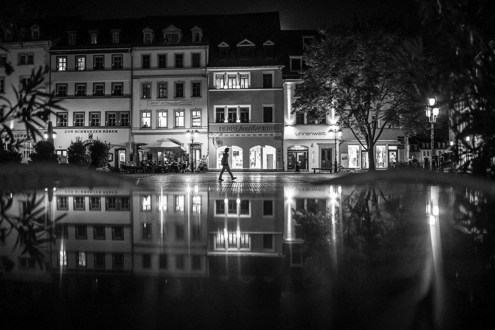 Weimarer Marktplatz bei Nacht. Die Spiegelung entsteht durch eine Metalltischplatte.