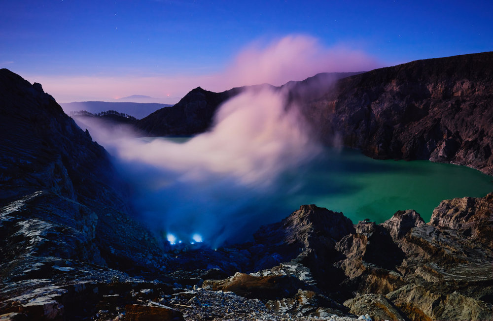 Kawah Ijen volcano crater lake with blue flame and sulfuric smoke view with sunrise dawn morning.
