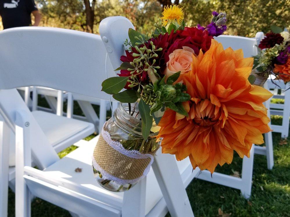 Aisle bouquet mason jar with bright flowers, Orange, burgundy and blush dahlias and roses. Highlands Estate.