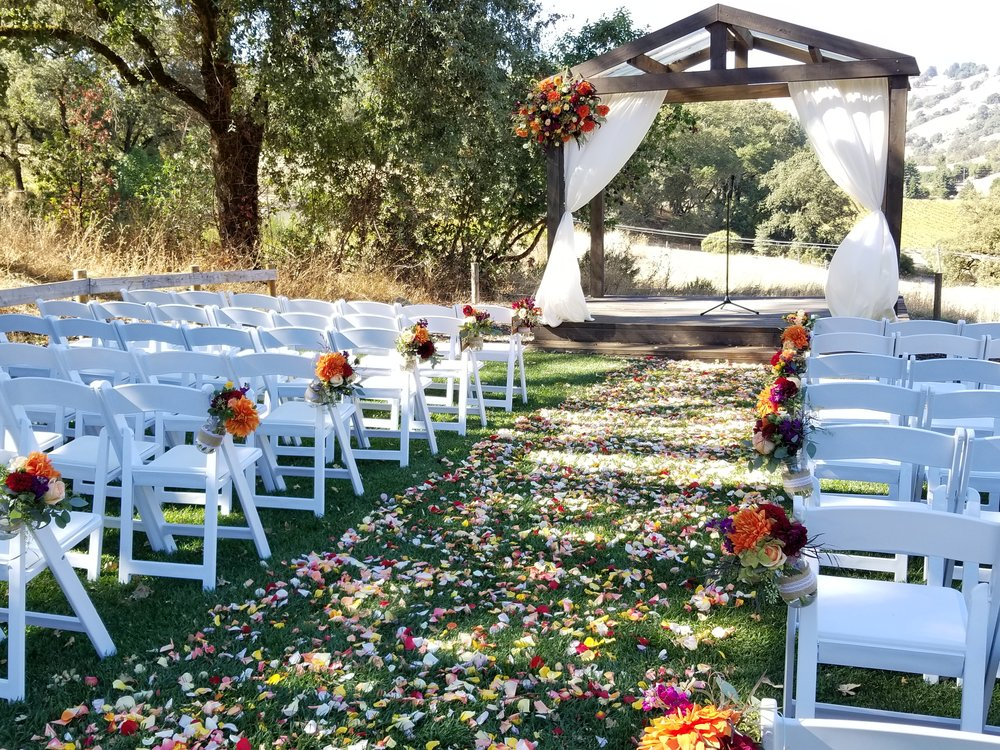 Wedding Arch and Aisle bouquets Highlands Estate, Sonoma Winery, Bright pops of fall color including burgundy and blush dahlia, ranunculus, roses and eucalyptus