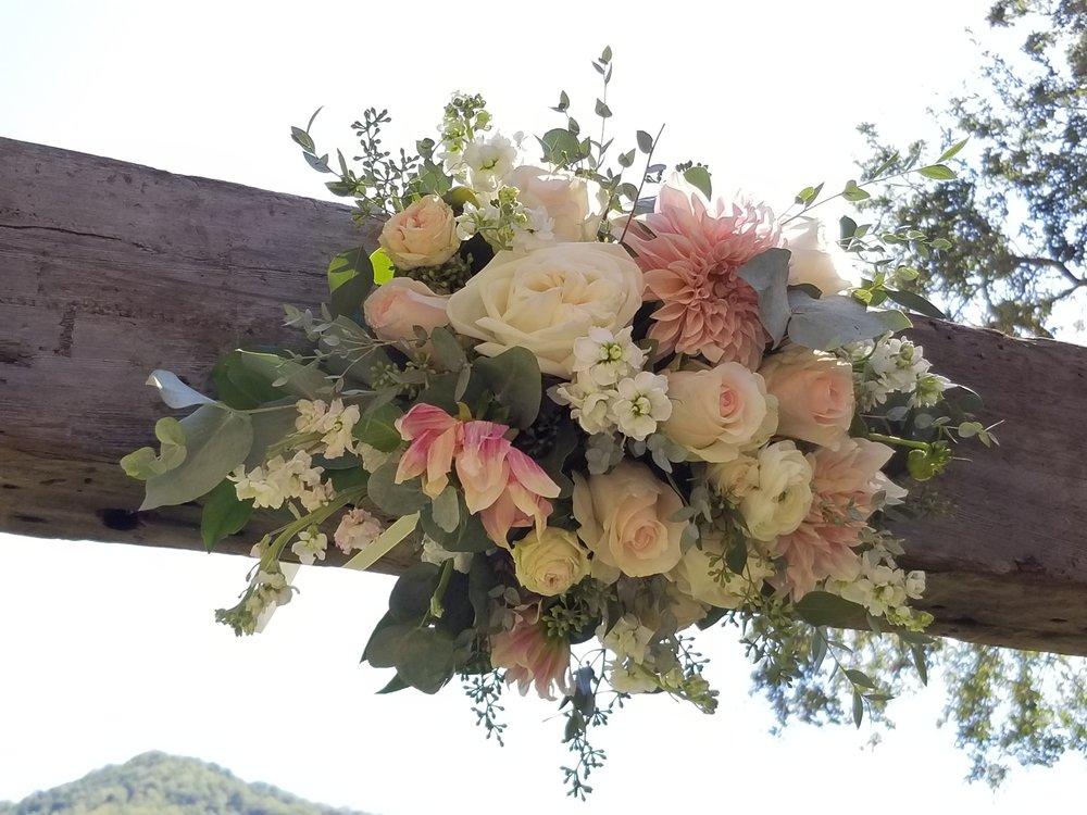 Central floral with blush, ivory and pink dahlias, ranunculus, garden roses and eucalyptus, Nelson Family Vineyard wedding arch