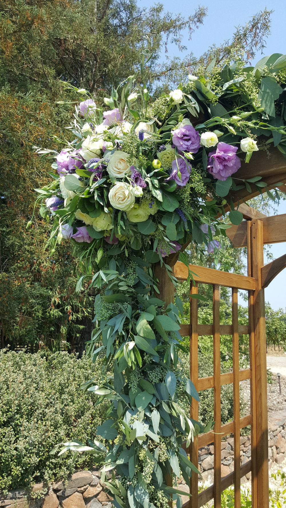Wedding arch purple, lavender and white roses and lisianthus with olive and eucalyptus greens. Wedding Arch Flowers DeLoach Winery