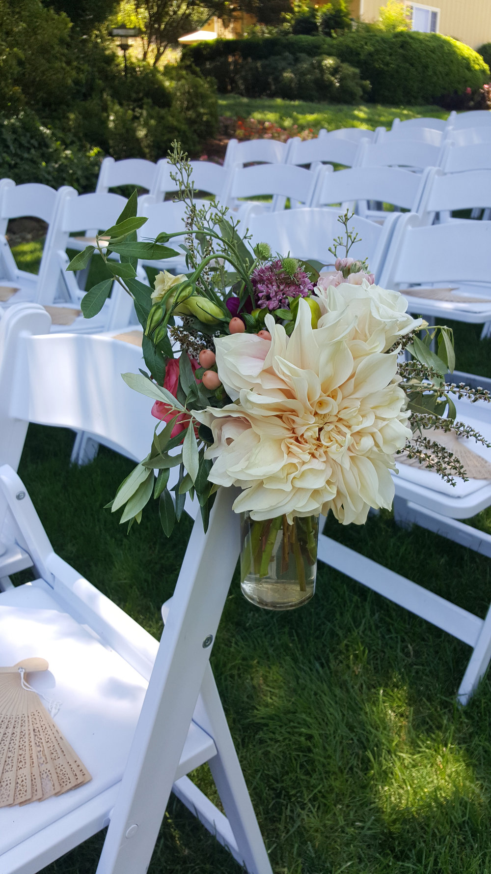 Mason jar tied to aisle with ribbon, dahlias and roses with eucalyptus, Aisle bouquet Sonoma wedding. Highlands Estate wedding ceremony flowers