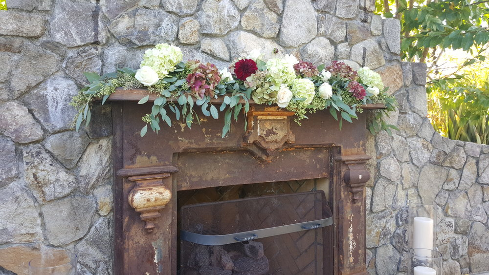 Garland decor on the rustic fireplace mantle. Eucalyptus greens with hydrangea, dahlia, roses and ranunculus., The General's Daughter fireplace ceremony