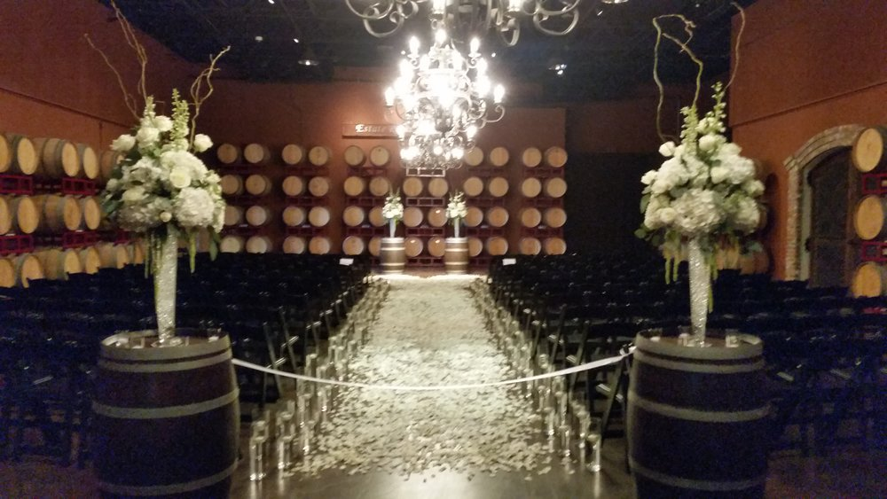 Wine cave ceremony, aisle lined with floating candles and rose petals. Wine barrel toppers of white and green., Palm Event Center wedding flowers wine cellar