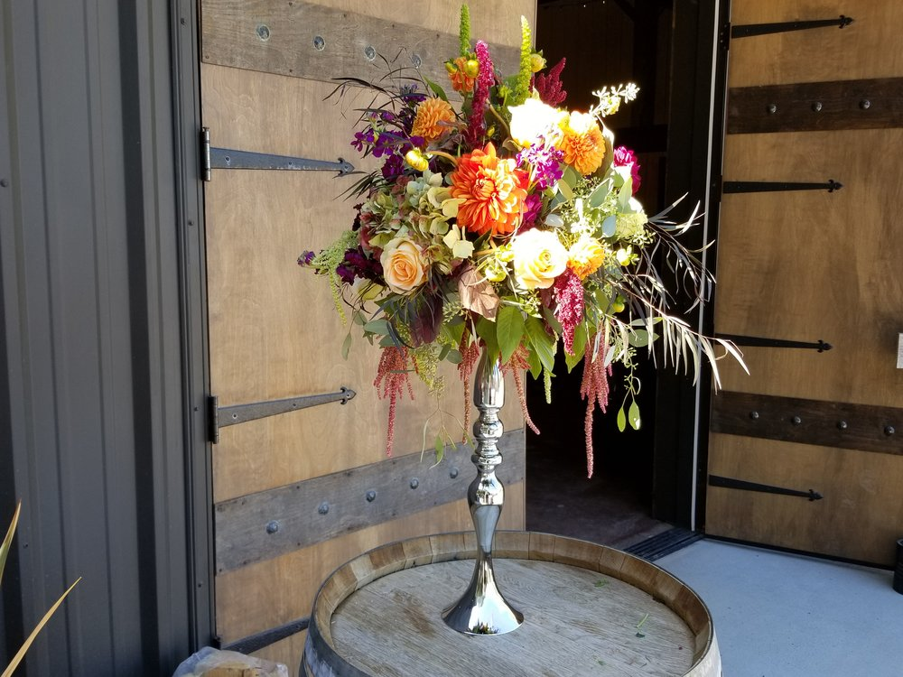 Wine barrel flowers on silver base, featuring orange, burgundy, blush and pink flowers. Sonoma County wedding reception. Highland Estate barn wedding.