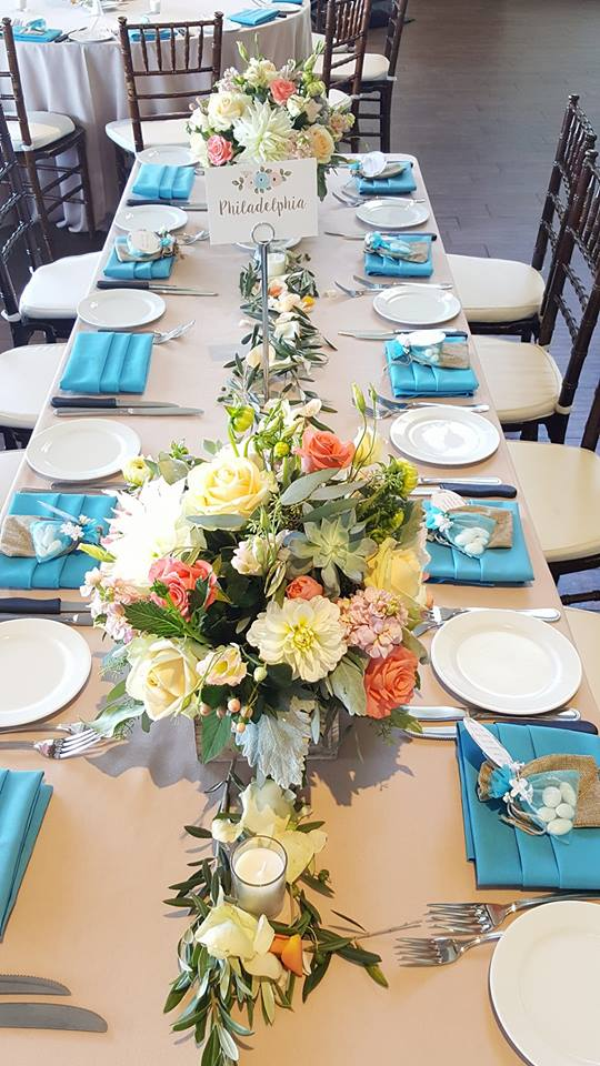 Rectangle tables, centerpiece in rustic wooden box with roses, ranunculus and greens. Eucalyptus and olive greens line length of table Chardonnay golf club wedding reception