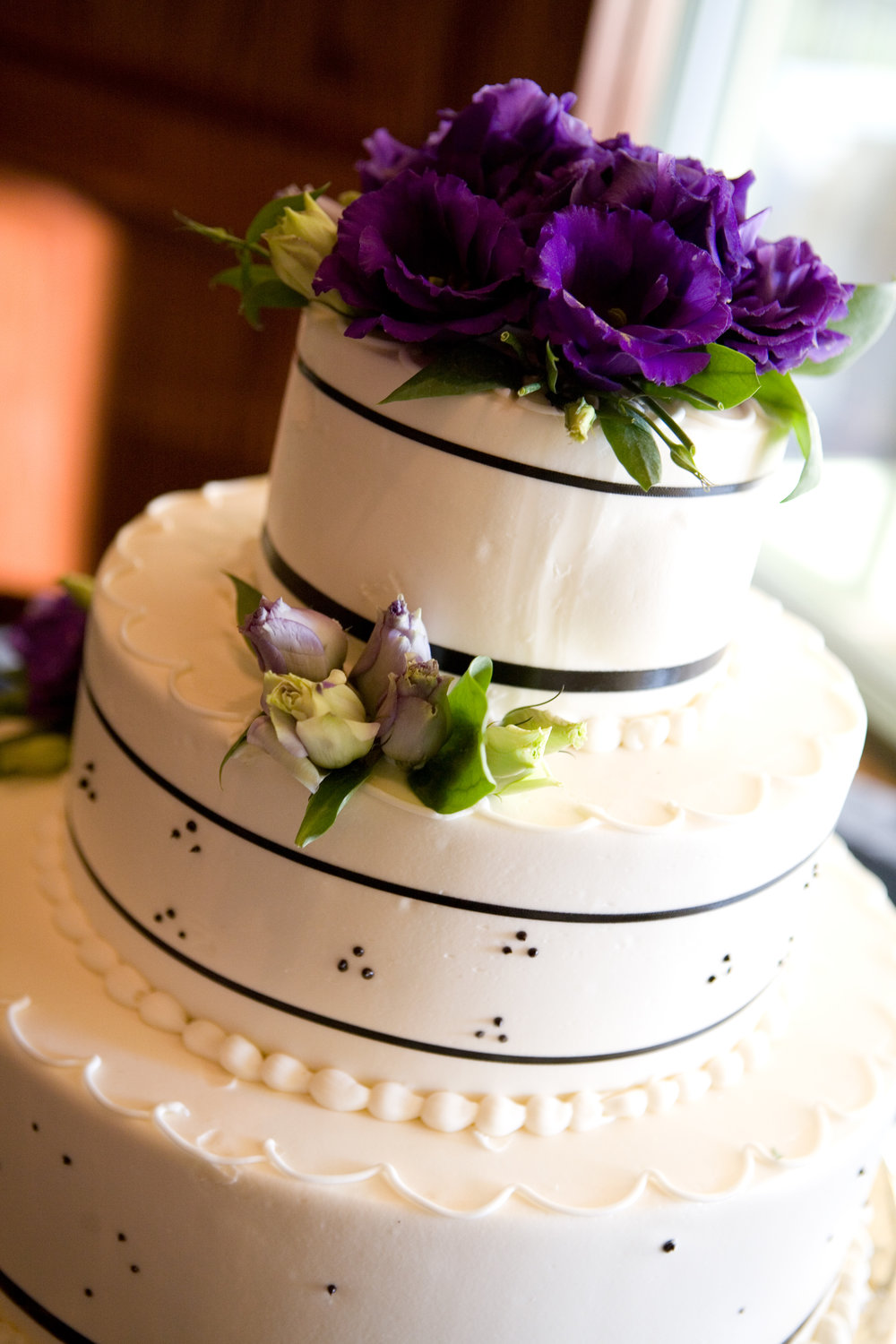 Purple lisianthus place on wedding cake. Wedding cake flowers in purple