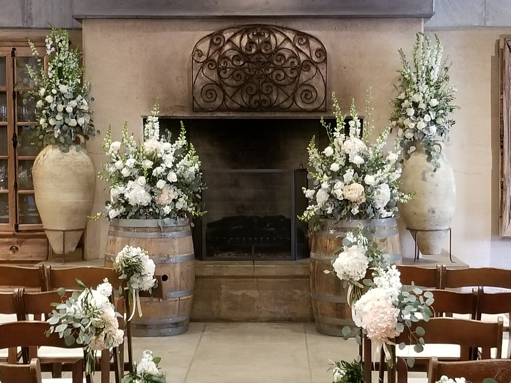 Romantic indoor wedding ceremony in front of the fireplace at Ramekins Sonoma. Altar flowers placed on urns and wine barrels, aisle lined with eucalyptus garland and lush white and blush flowers.