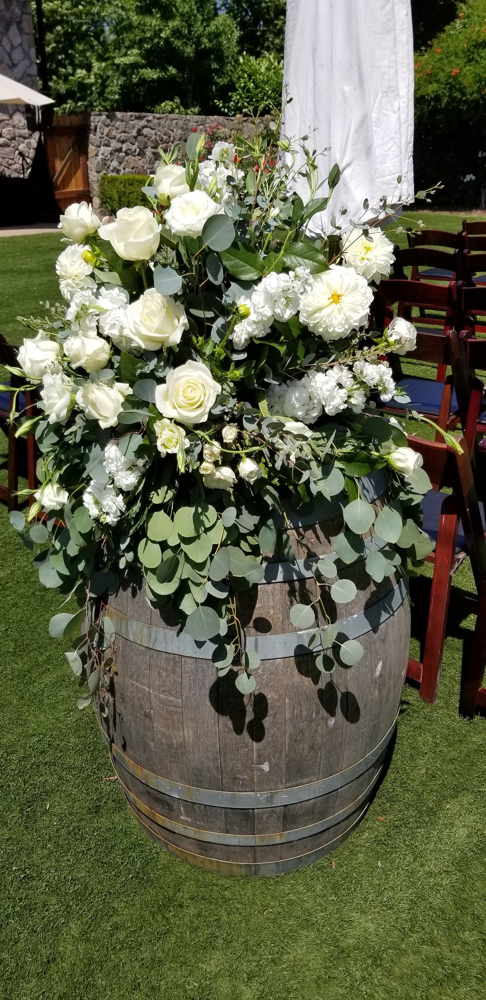 Wine barrel topper, flowing eucalyptus greens and white flowers featuring dahlia, hydrangea and roses at The Lodge Sonoma wedding ceremony.