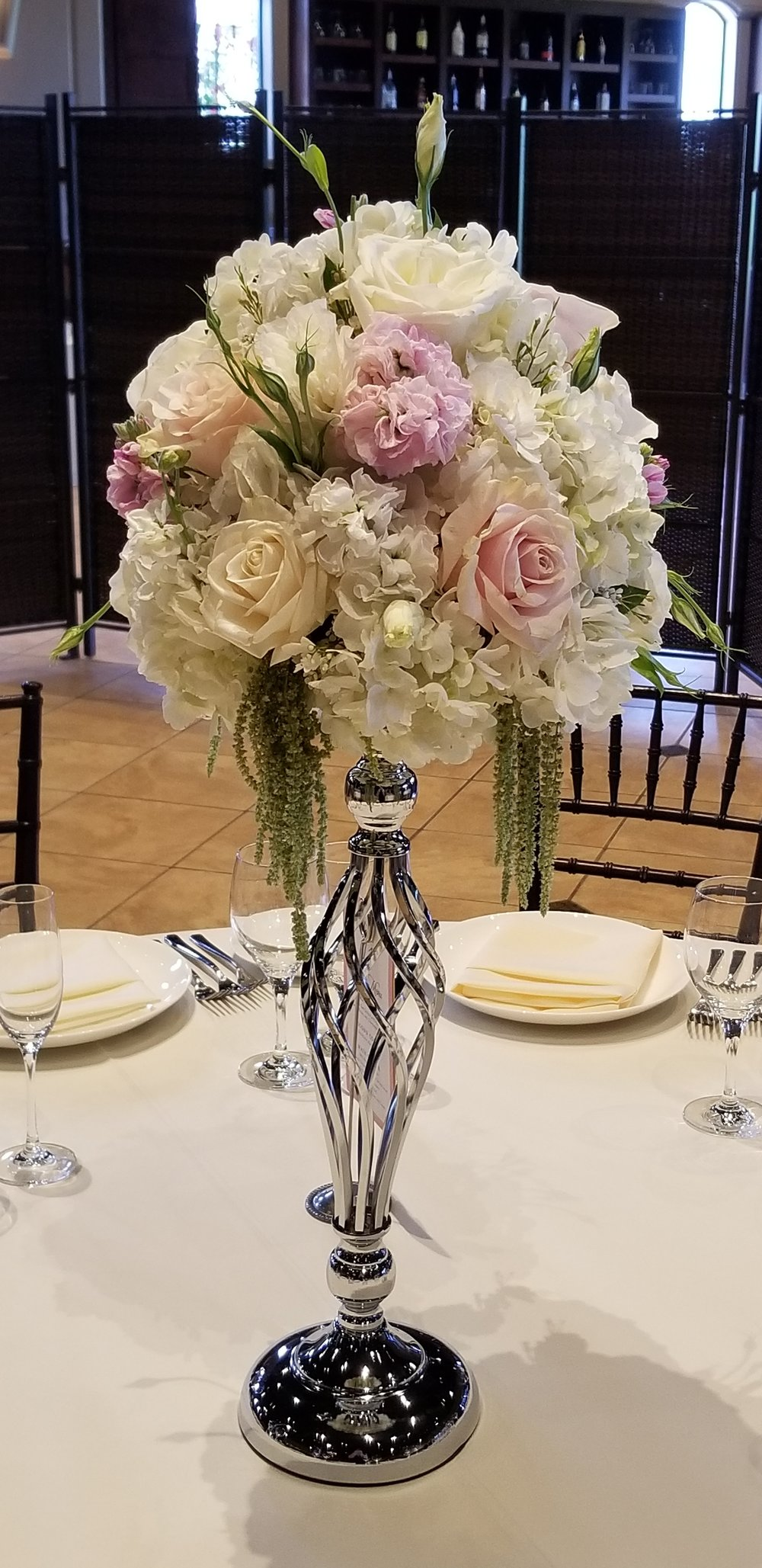 Reception centerpiece, tall and romantic silver riser with a spray of romantic blush, white and pink flowers. Palm Event Center wedding reception flowers.