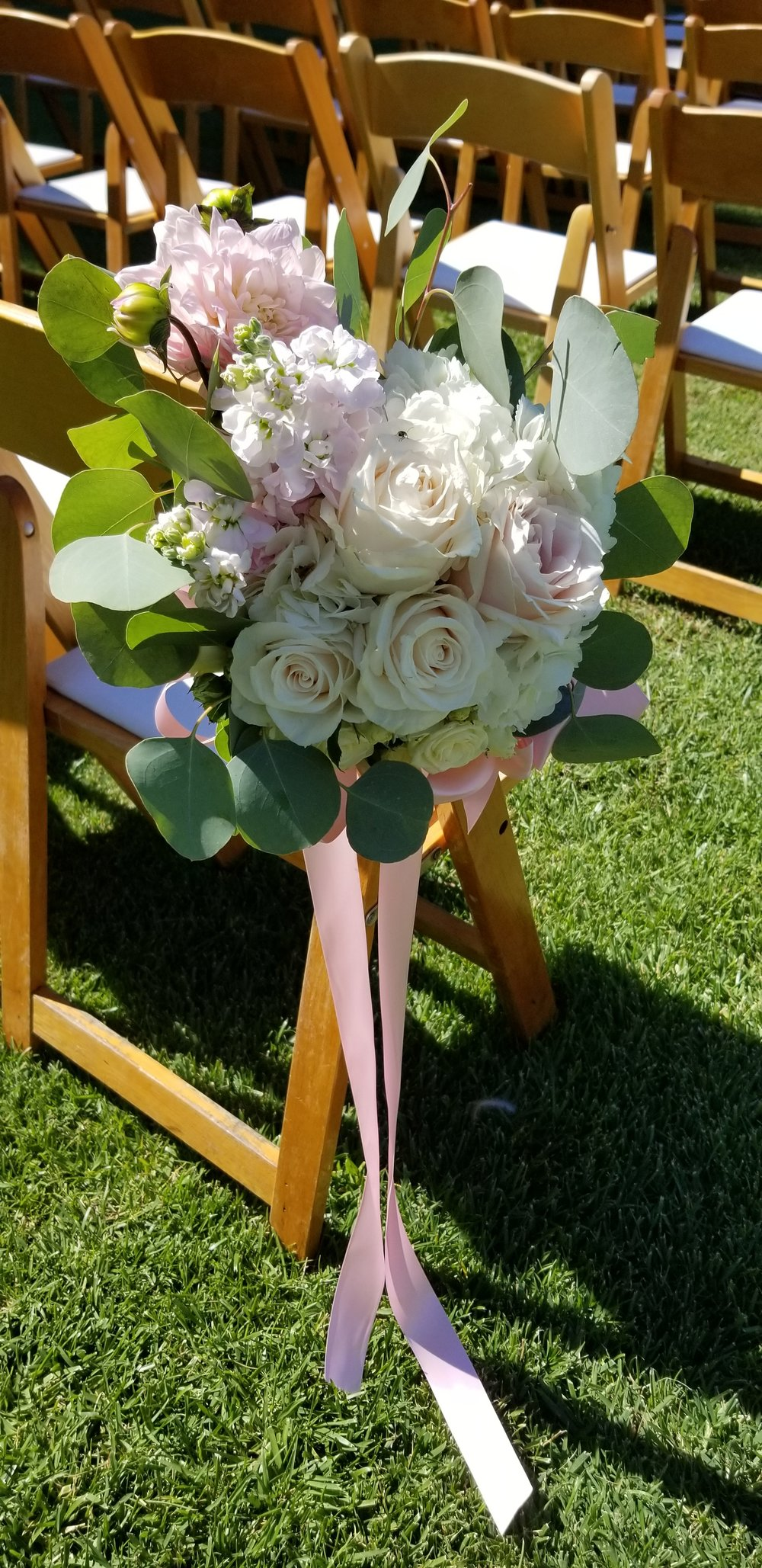 Wedding aisle bouquet in blush and white with draping greens, tied to aisle chairs with flowing ribbon.