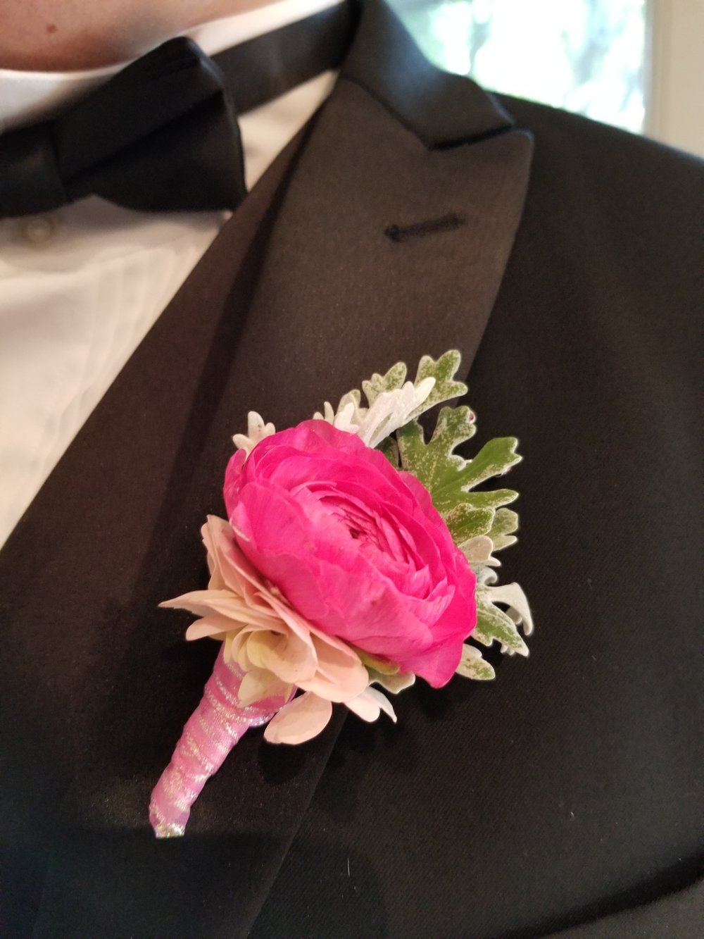 Groom boutonniere in pop of fuchsia featuring ranunculus and dusty miller.