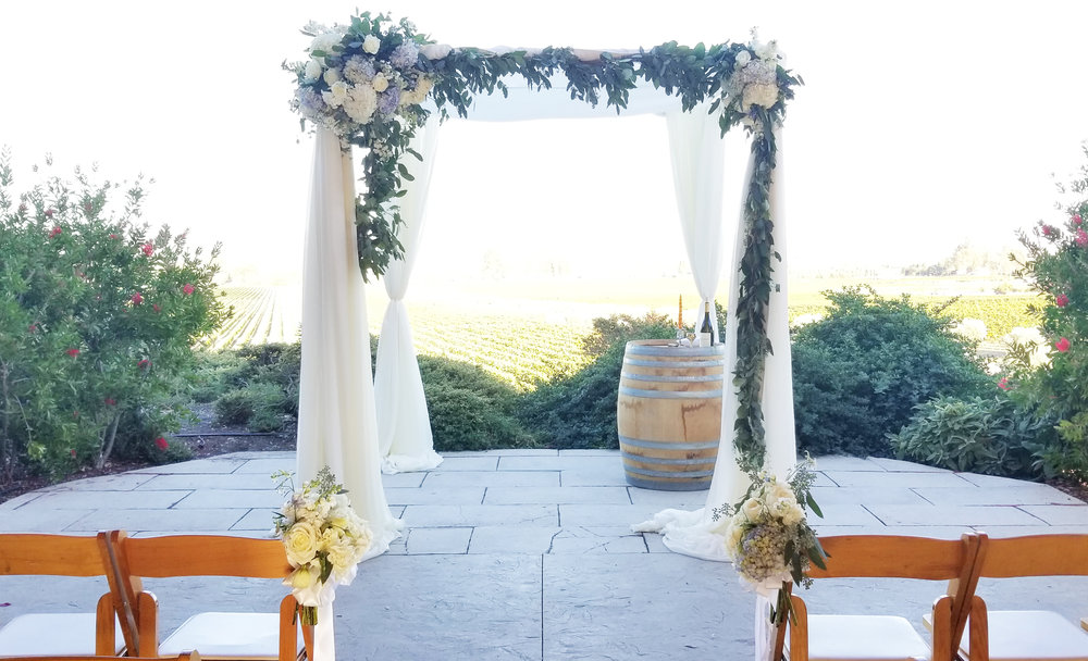 Gloria Ferrer patio wedding ceremony, chuppah draped in sheer white with flowing greenery, blush and white flowers.