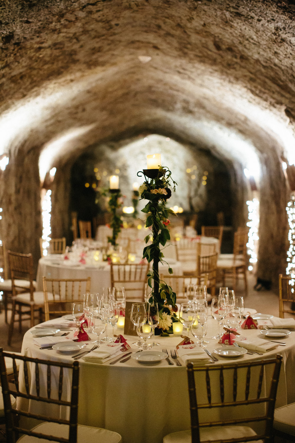 Hans Fahden wine cave reception, candelabras dressed up with green vines and pink passion flowers.