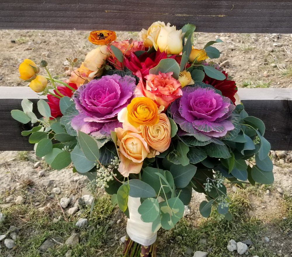 Bright and moody bridal bouquet, flowers include ranunculus, garden roses and purple cabbage leaf, seeded eucalyptus greenery. Hand gathered and tied with satin ribbon.