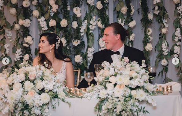 Sweetheart table floral backdrop, draping vines and white flowers. Oxford Suites reception