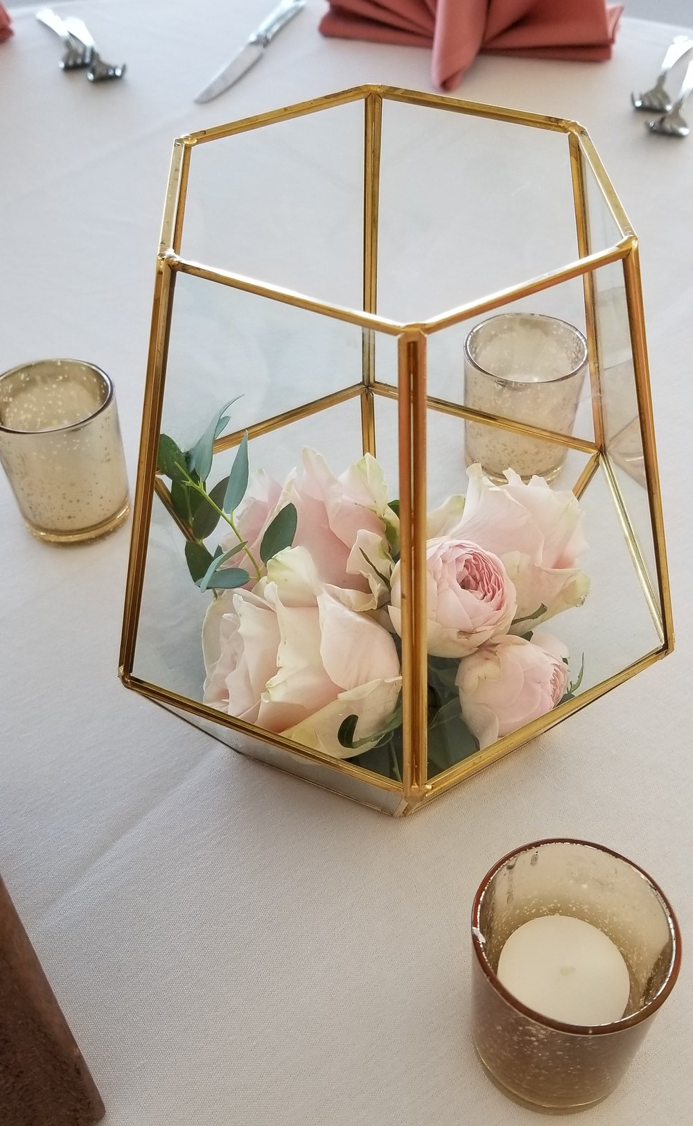 Clear terrarium centerpiece with blush pink flowers and a sprig of greenery surrounded by gold mercury candles. Eagle Vines Golf Club.