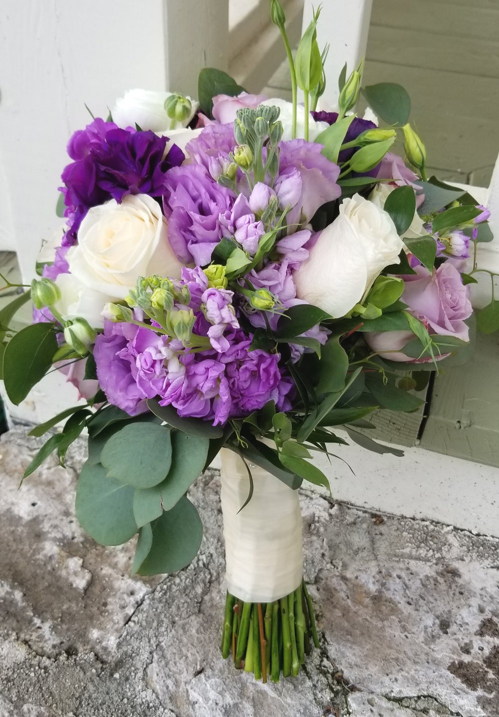 Bridal bouquet featuring soft white roses and ranunculus and vibrant purple lisianthus, accented with dollar eucalyptus greens. Hand gathered and tied with white satin ribbon.