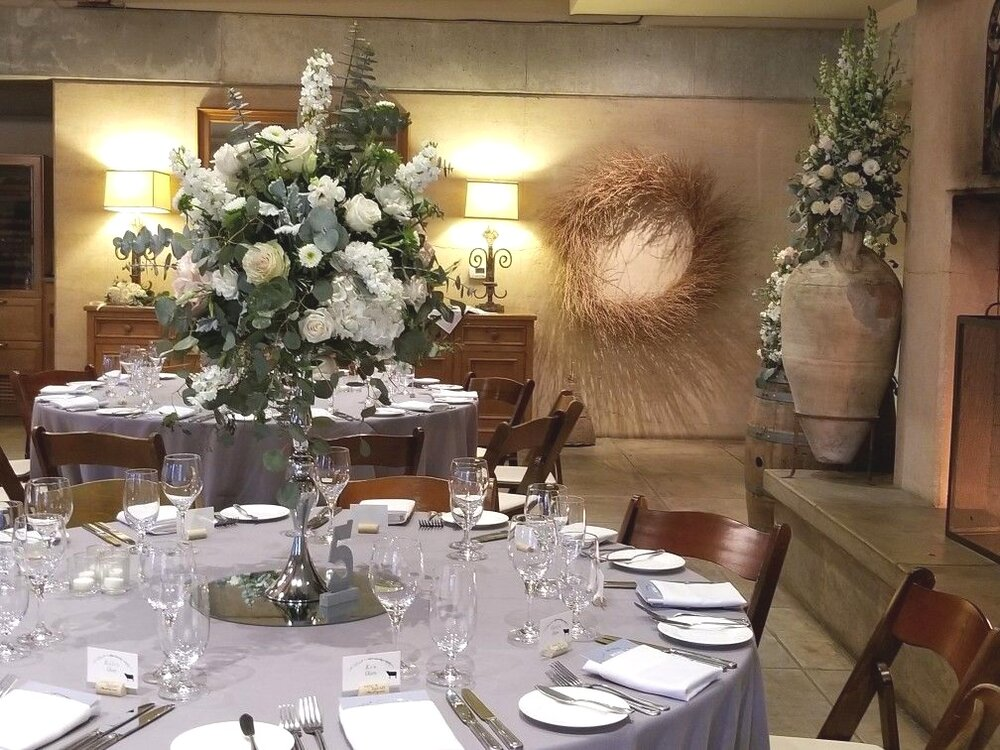 Silver floral riser, tall wedding centerpiece with romantic white flowers and draping eucalyptus greens. Ramekins Sonoma wedding reception.