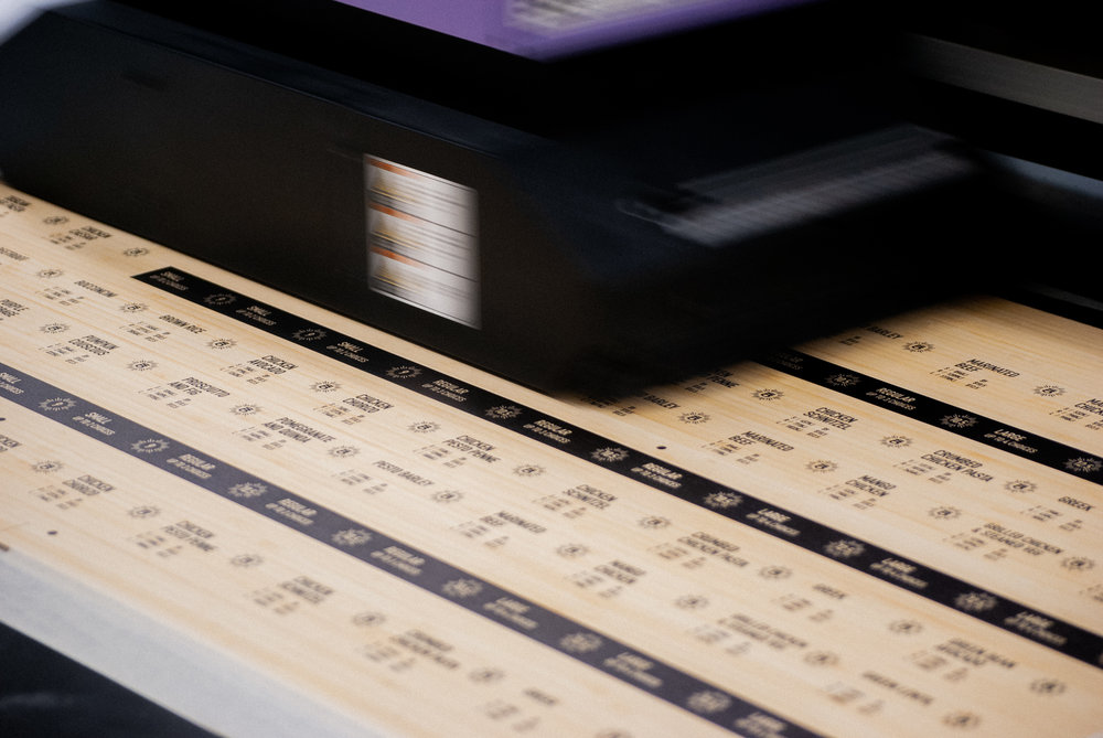 Flatbed Printing - Our flat bed printer changes the traditional rules of print. It allows us to print on virtually any substrate up to 1200x2400mm in size so long as it's less than 50mm thick. You read that right... up to 1.2 x 2.4 metres in size, and up to 5cm thick.We use this machine to print lots of things - thick wood, acrylic, thick paper, coreflute, forex, aluminium composite and so much more.Our flat bed printer is also kitted up with white ink and clear ink. We use white ink as a base-colour or a spot-colour (ie. white graphics/text) and we use clear ink as a top-coating for protecting hard-wearing product or as a subtle special finish.We run a Mimaki JFX-200. That's because we think its quality and ability to produce fine detail is unsurpassed in the industry. It prints with UV cured inks which means they are outdoor rated and lightfast.