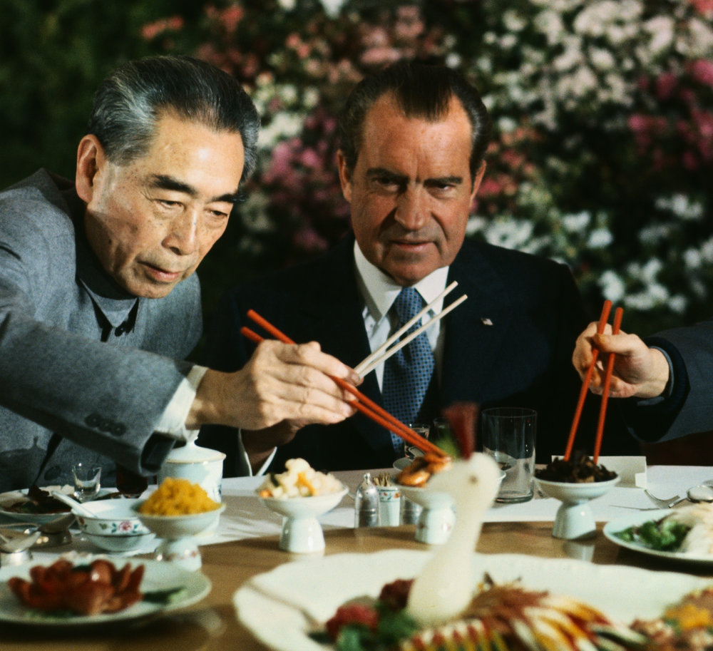 ‍February 27,1972, Shanghai, China — President Nixon holds his chopsticks in the ready position as Premier Chou En-lai (left) and Shanghai Communist Party leader Chang Chun-chiao reach in front of him for some tidbits at the beginning of the farewell banquet here. — Image by © Bettmann/CORBIS