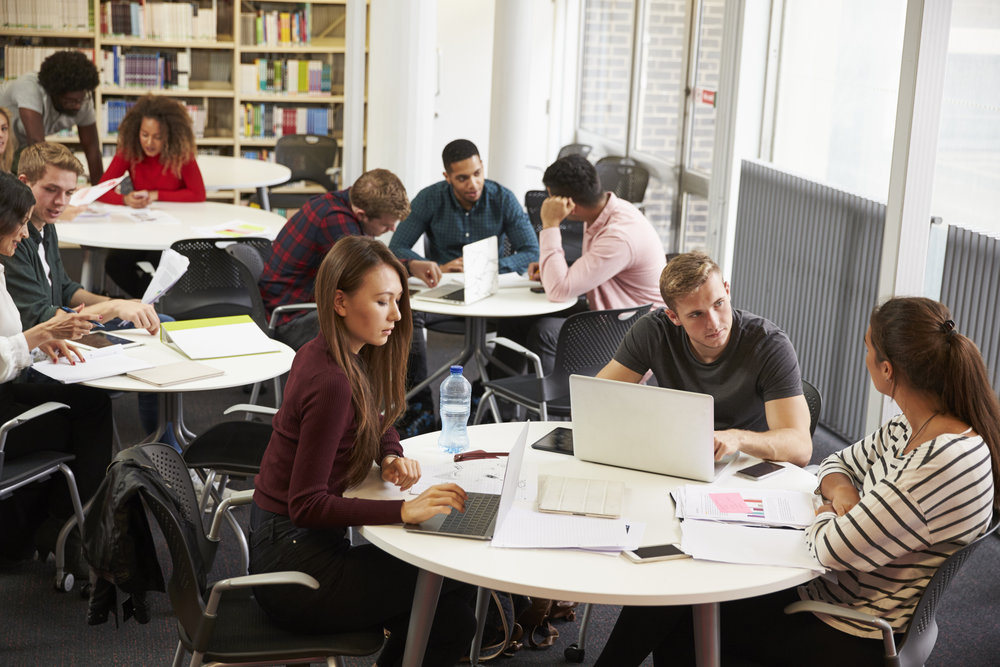 busy-university-library-with-students-and-tutor-PSFDK2A.jpg