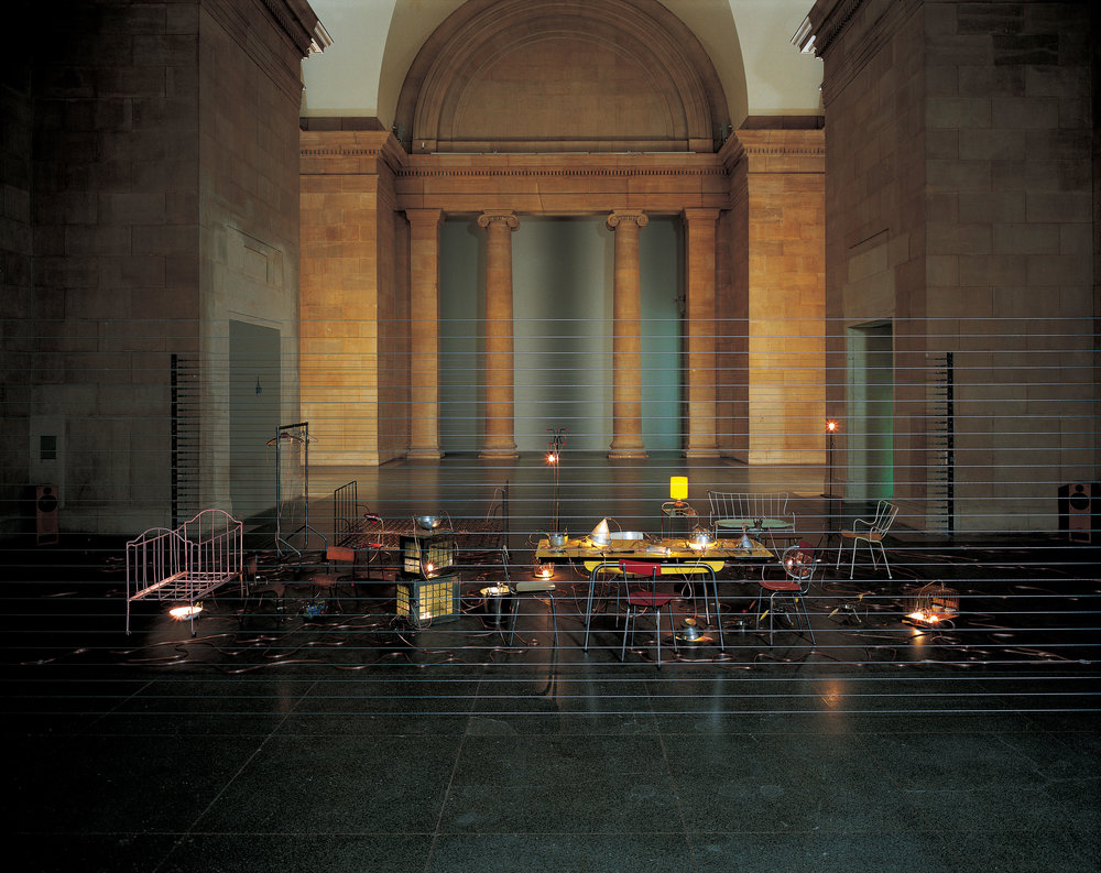 Homebound (2000) Mona Hatoum,mixed-media installation with kitchen utensils, furniture, electric wire, light bulbs, computerized dimmer unit, amplifier and speakers. Installation view at Duveen Galleries in Tate Britain, London, 2000. Photo by Edward Woodman. Courtesy the artist and Galleria Continua, San Gimignano/Beijing/Le Moulin.