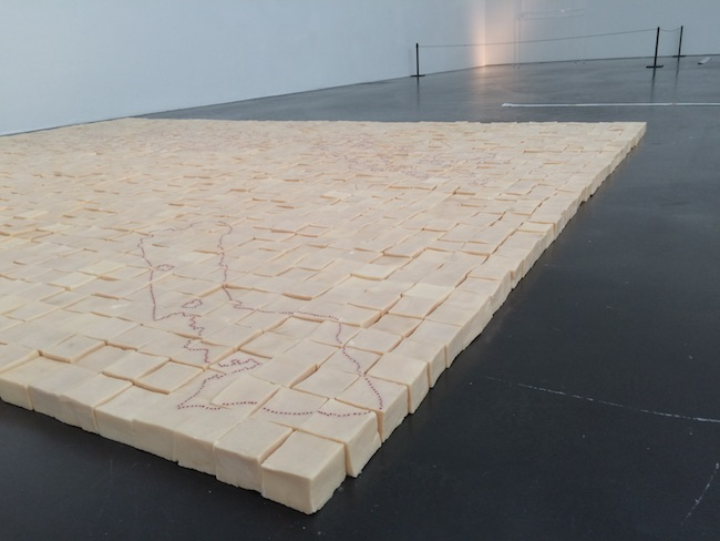 Mona Hatoum. Present Tense, 1996/2011. Photo: Paula Lūse. The work is made up of 2200 blocks of olive oil soap, a traditional Palestinian product from Nablus, a town north of Jerusalem. The drawing on the soap blocks, created by tiny red glass beads pushed into their surface, depicts the map of the 1993 Oslo Peace Accord between Israel and the Palastinians. The beads delineate the territories to be handed back to the Palastinian authority.