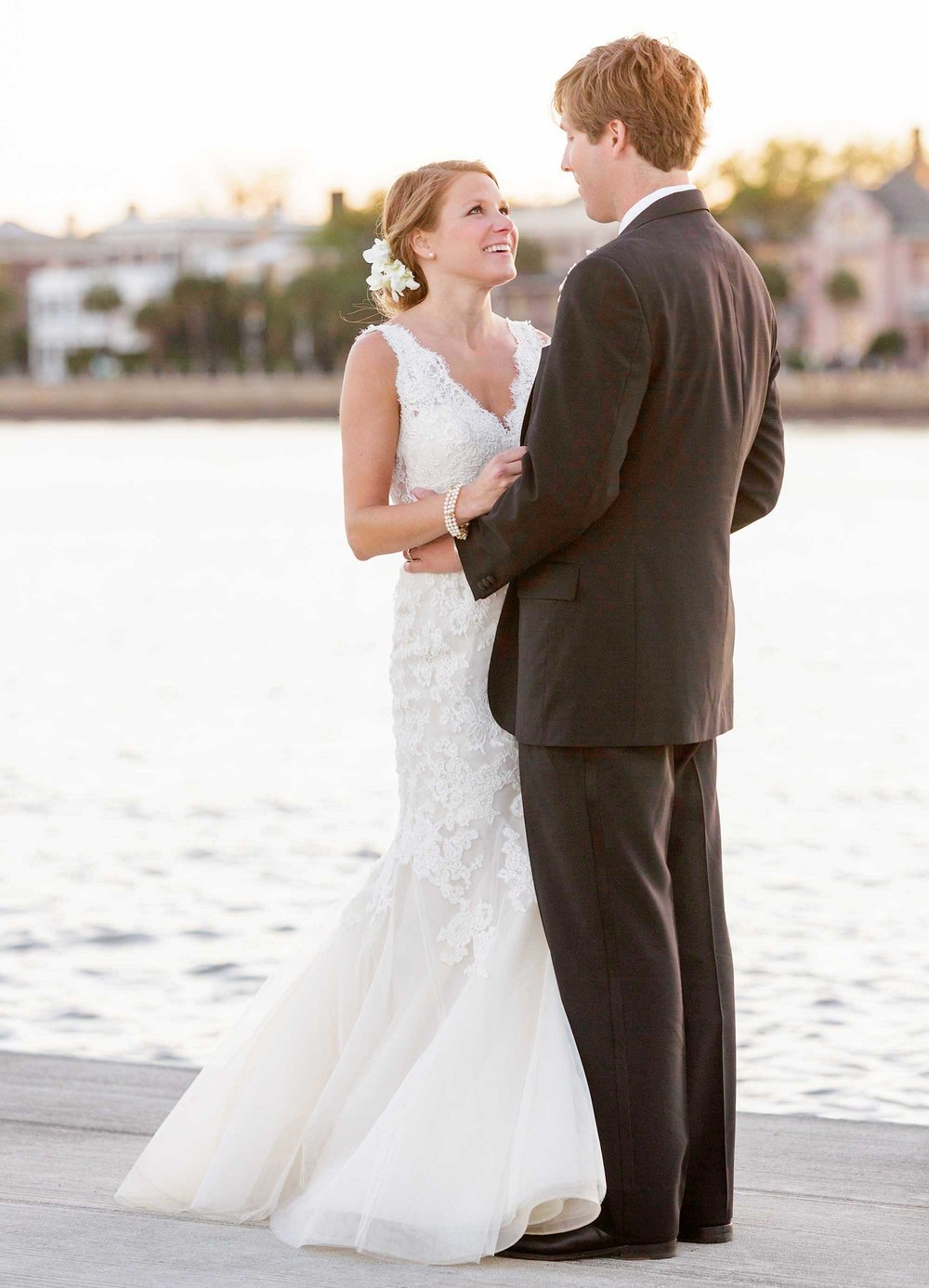 A newly married couple hug on a dock.