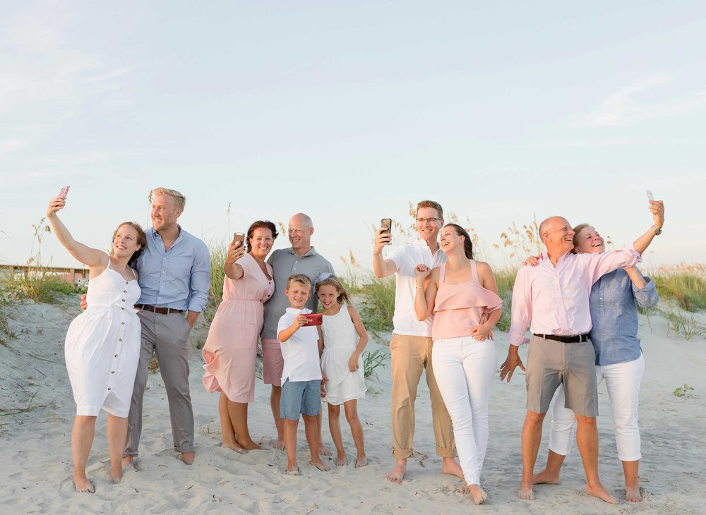 Funny family beach portrait on the Isle of Palms. People holding cellphone in a family portrait.