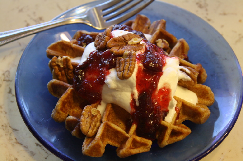 Top the waffles with the cranberry-maple syrup, whipped cream, and pecanas