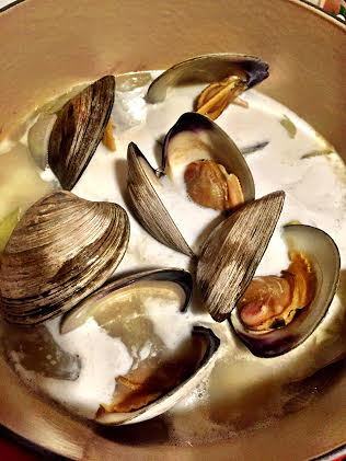 Once the clams open, add the coconut milk and simmer for 15 minutes.