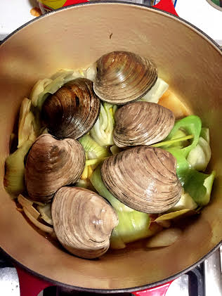 Add the clams and wine and cook until the clams open.